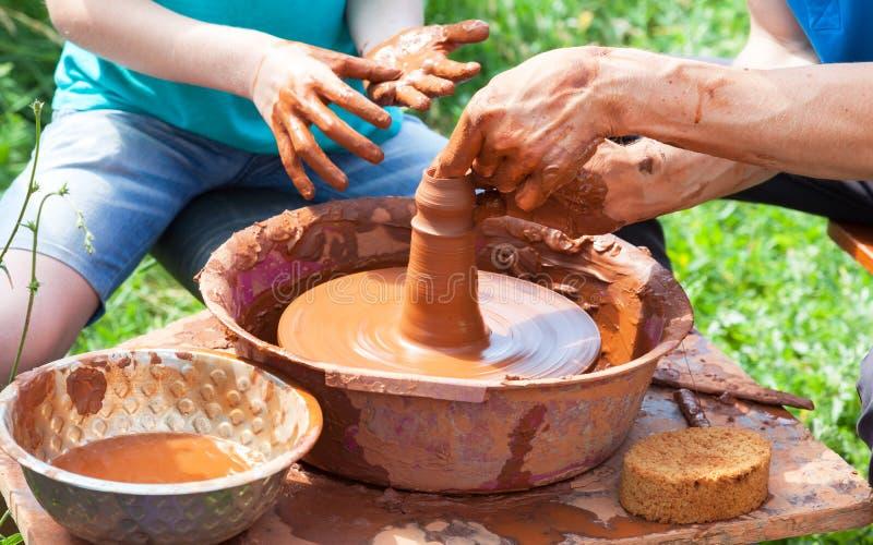 Läraren hjälper hans student att arbeta med röd lera arkivbilder