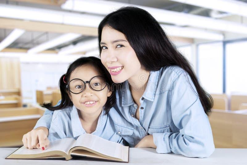 Läraren hjälper hennes student att studera i grupp royaltyfria bilder