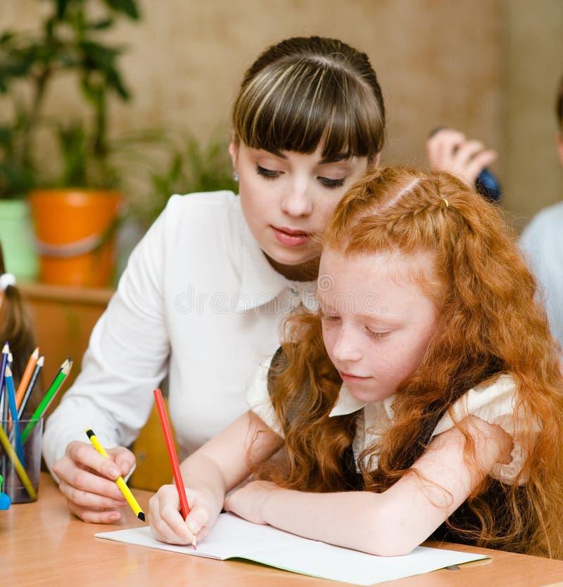 Läraren hjälper studenten med schoolwork i skolaklassrum royaltyfri fotografi