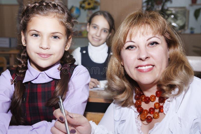 Läraren hjälper studenter royaltyfri bild