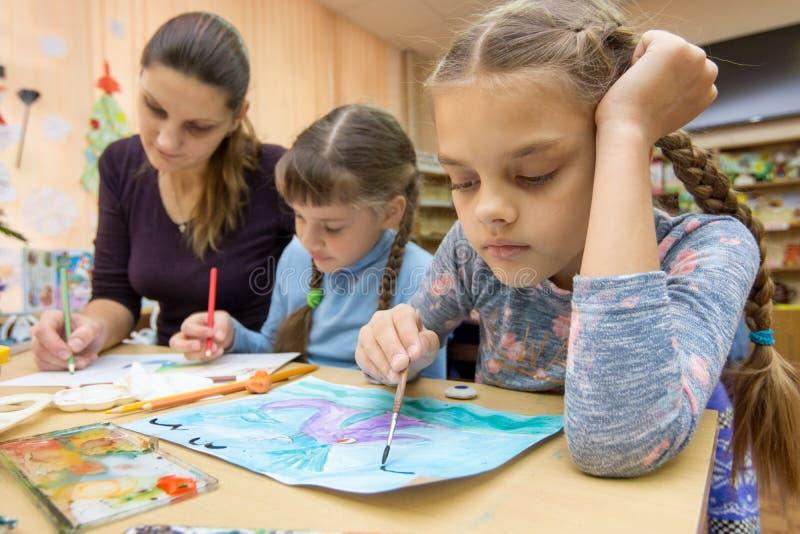 Läraren hjälper studenterna i dra grupp arkivbild