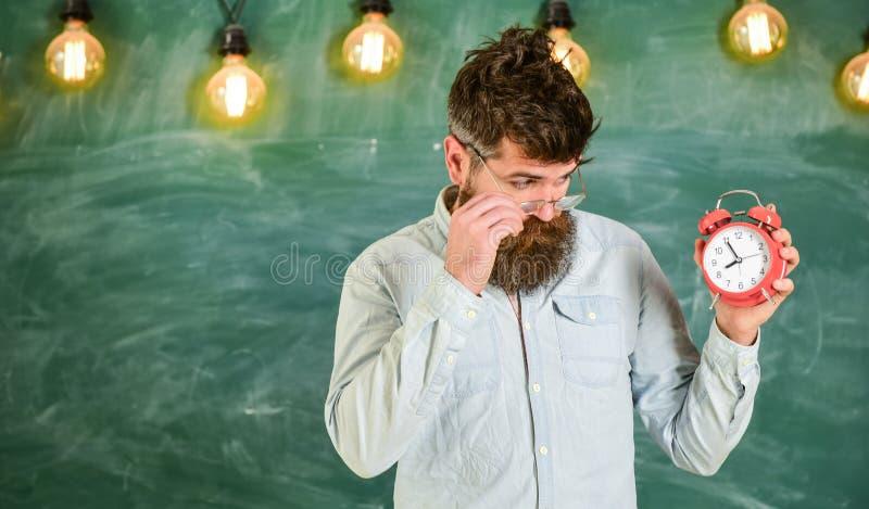 Läraren i glasögon rymmer ringklockan Skolaschemabegrepp hållande ringklocka för manlig lärare, kontrolltid _ royaltyfri fotografi