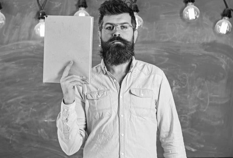 Läraren i glasögonhåll bokar i handen, kopieringsutrymme Mannen med skägget och mustaschen på lugna framsida står i klassrum royaltyfria foton