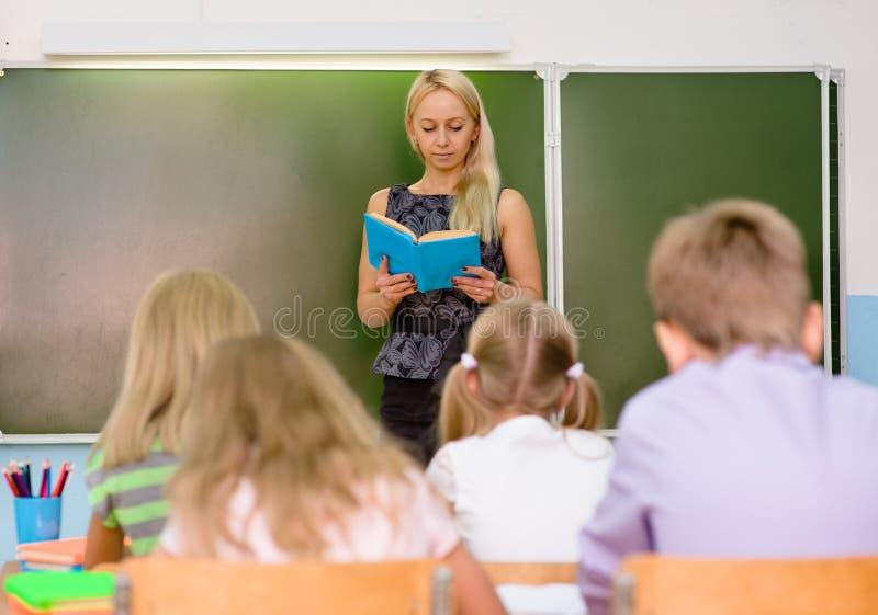 Läraren läser studenterna en bok royaltyfri foto