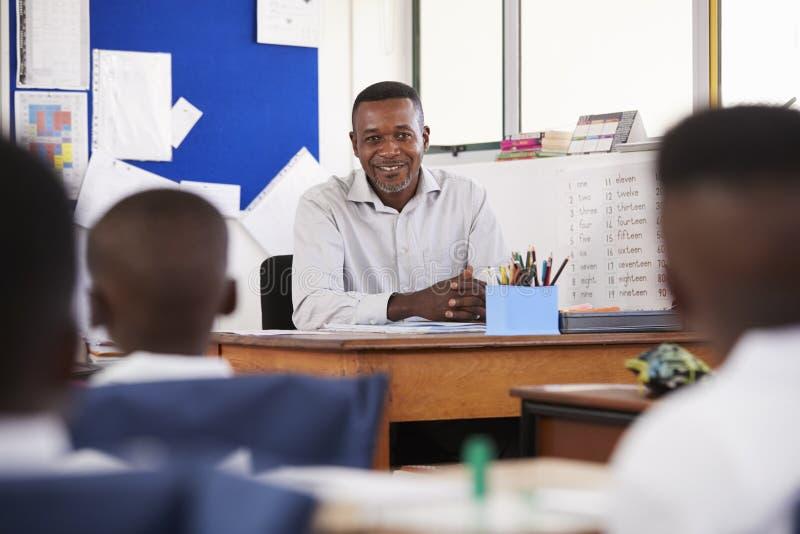 Läraren ler på ungar från hans skrivbord i elementärt klassrum royaltyfri foto