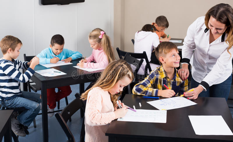 Läraren och den elementära åldern lurar teckningen på klassrumet royaltyfria bilder