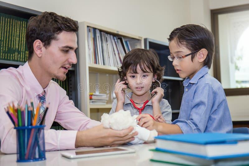 Läraren och studenter spelar doktorn med stetoskopet arkivfoto