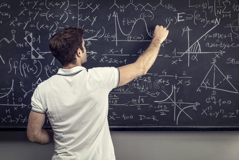 Läraren skriver på svart tavla arkivbilder