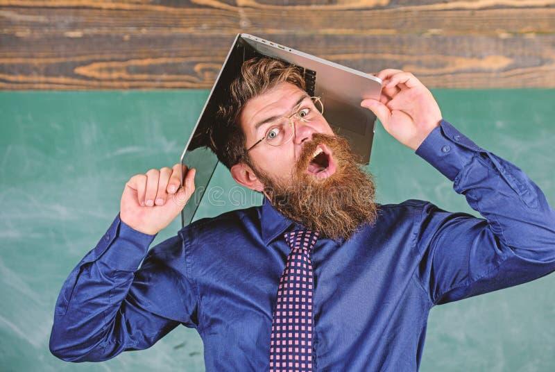 Läraren uppsökte mannen med modern svart tavlabakgrund för bärbara datorn Skolan blåser hans mening Hipsterlärare som är aggressi fotografering för bildbyråer