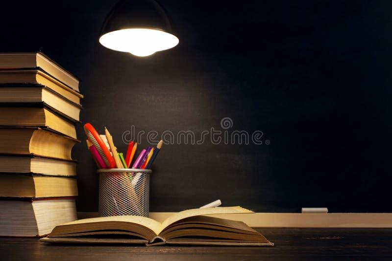 Lärarens skrivbord eller arbetare, som de skrivande materialen ligger på, böcker, i aftonen under lampan Mellanrum för text eller royaltyfria foton
