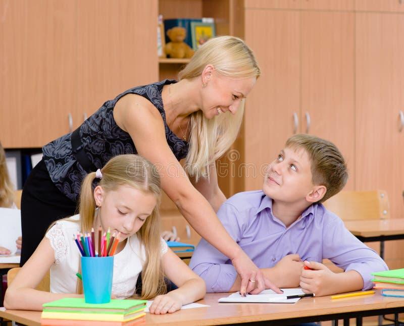 Lärareportioneleven förklarar hur man löser uppgiften royaltyfri foto