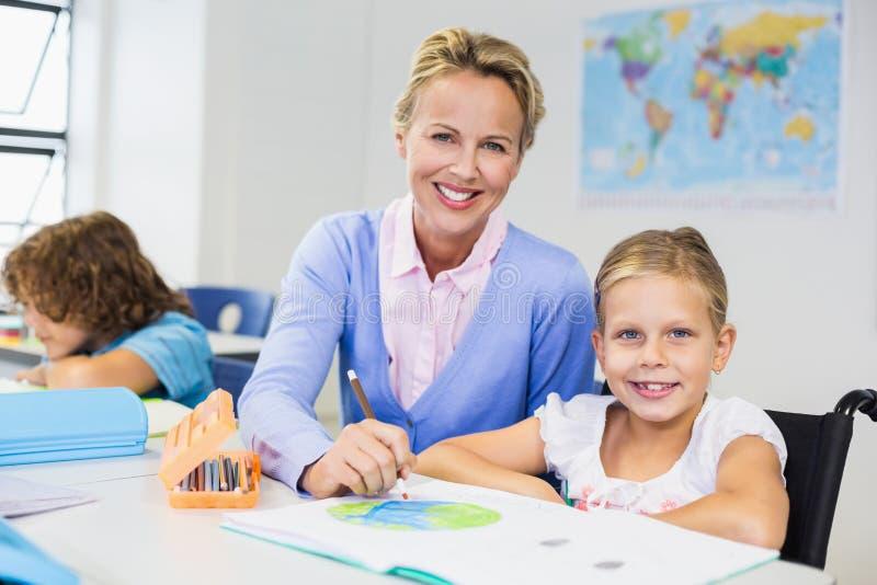 Lärareportionskolflicka med hennes läxa i klassrum arkivfoton