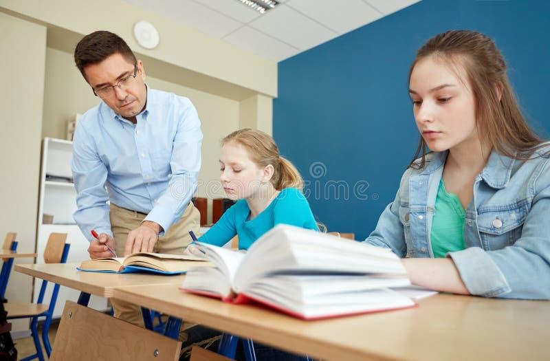 Lärareportionstudenter med uppgift på skolan royaltyfri foto