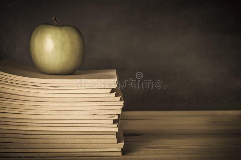 Lärares skrivbord - Apple på böcker royaltyfri foto