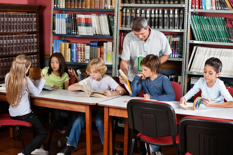 LärareShowing Book To skolpojke i arkiv arkivbild