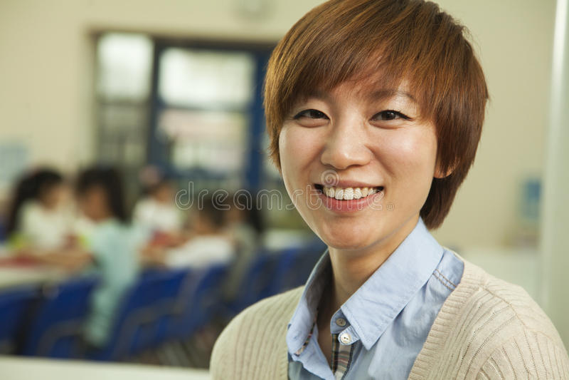 Lärarestående på lunch i skolakafeteria royaltyfri foto