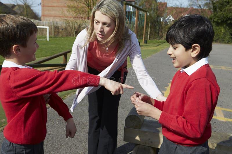 LärareStopping Two Boys stridighet i lekplats royaltyfri bild