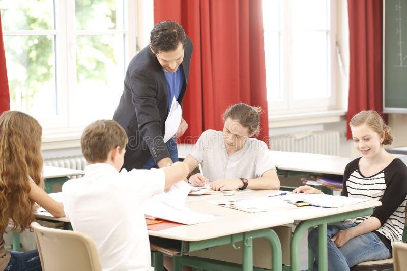Lärareundervisning eller utbildar på brädet en grupp i skola royaltyfri fotografi