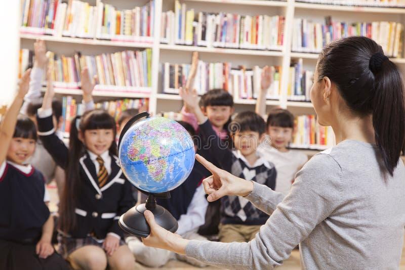 Lärareundervisninggeografi till skolbarn med ett jordklot arkivbilder