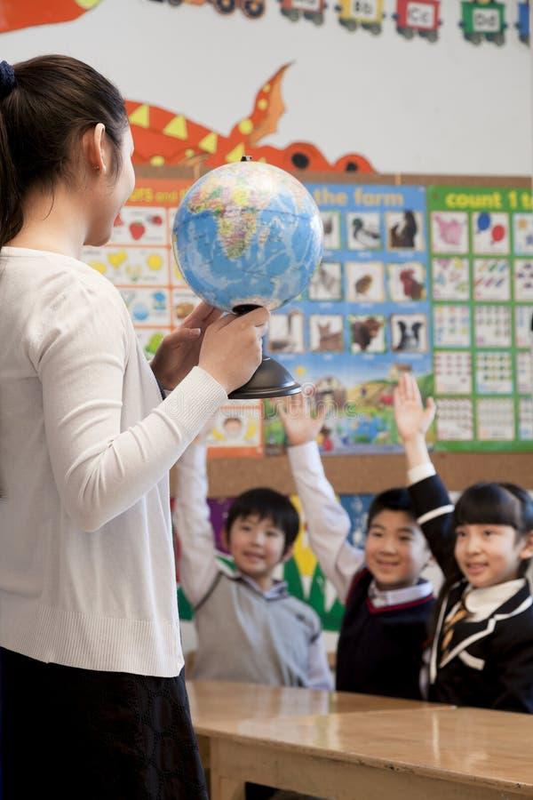 Lärareundervisninggeografi till skolbarn med ett jordklot arkivbild