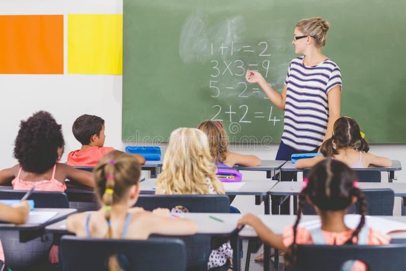 Lärareundervisningmatematik till skolaungar i klassrum arkivbild