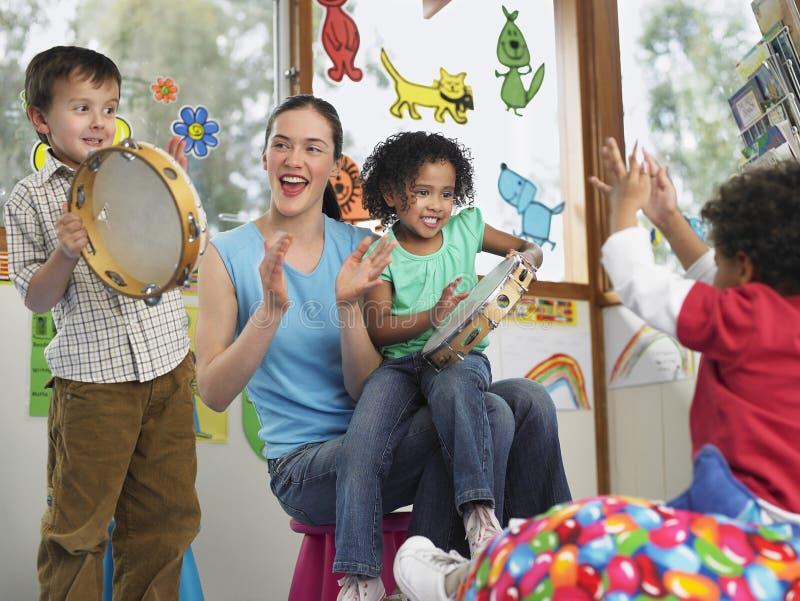 LärareWith Children Playing musik i grupp royaltyfri bild