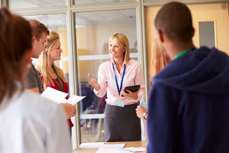 LärareWith College Students anseende vid skrivbord i klassrum royaltyfri fotografi