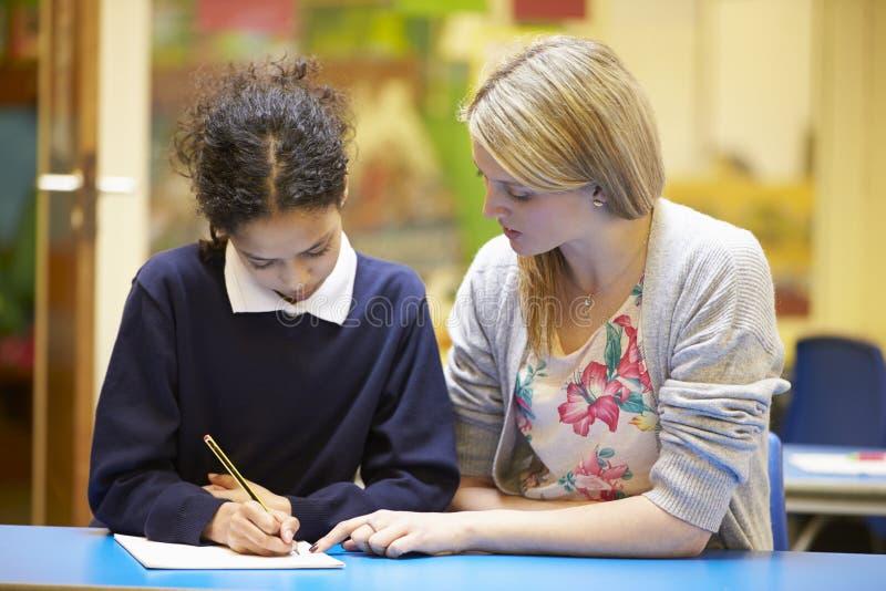 LärareWith Female Pupil läsning på skrivbordet i klassrum arkivbilder