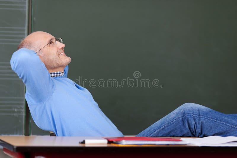 LärareWith Hands Behind huvud som ser upp på skrivbordet royaltyfri bild