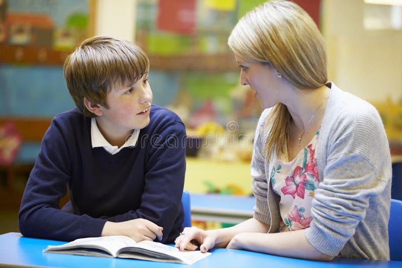 LärareWith Male Pupil läsning på skrivbordet i klassrum arkivfoto