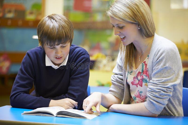 LärareWith Male Pupil läsning på skrivbordet i klassrum fotografering för bildbyråer