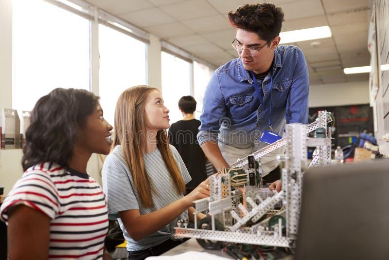 LärareWith Two Female högskolestudenter som bygger maskinen i vetenskapsrobotteknik eller teknikgrupp royaltyfria foton