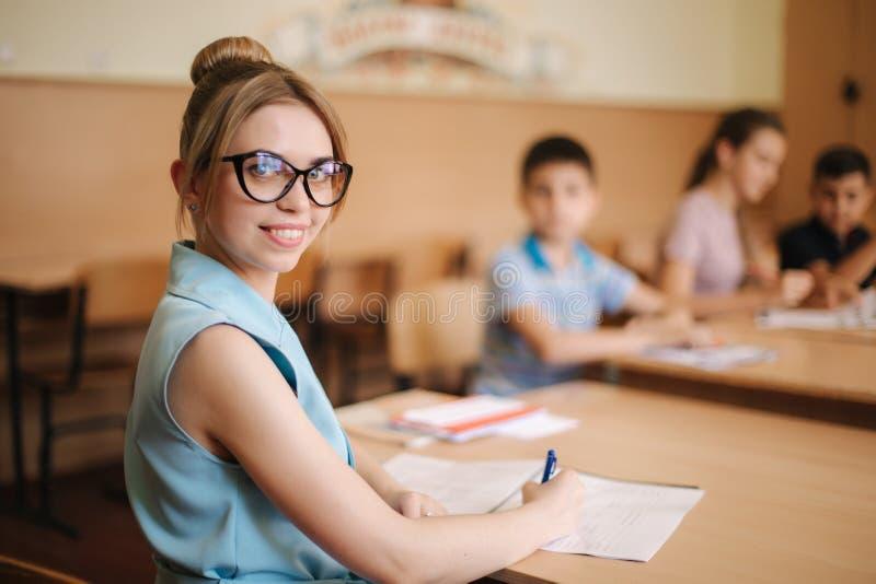 Lärarinna framme av barn Nätt lärare i klassrumet som sitter på skrivbordet och frågar barn Utbildning royaltyfria foton