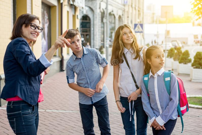 Lärarinna med barn som står den utvändiga skolan royaltyfri fotografi