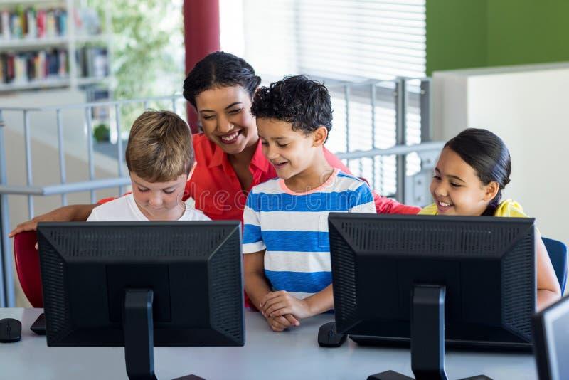 Lärarinna med barn under datorgrupp arkivfoto