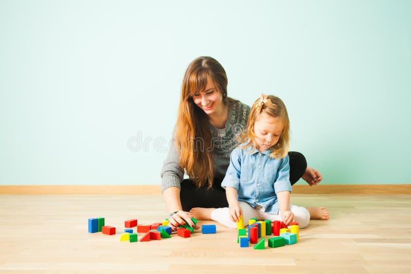 Lärarinna och gullig flicka som lär sammanträde på ett golv fotografering för bildbyråer