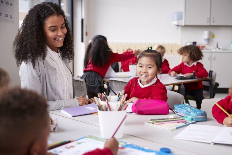 Lärarinna och kinesisk skolflicka som sitter på en tabell i en grupp för begynnande skola som ler till andra ungar, selektiv foku arkivbild