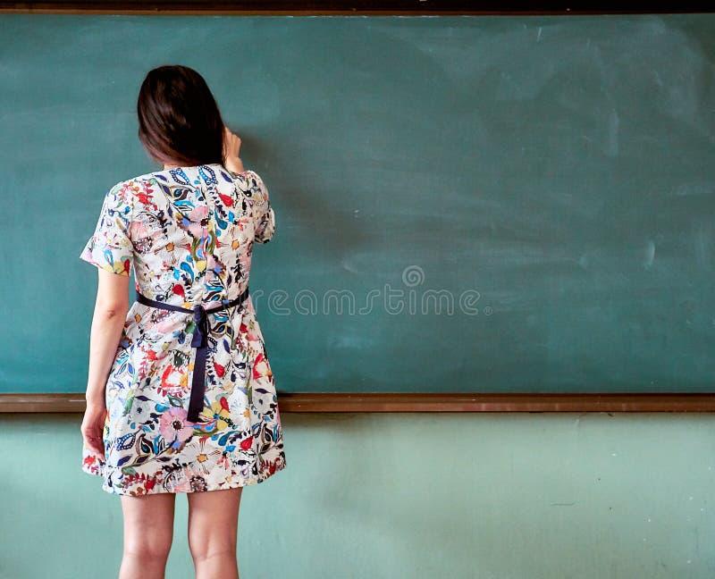 Lärarinna på en grundskola i Sydkorea som poserar för att skriva något på svart tavla royaltyfri fotografi