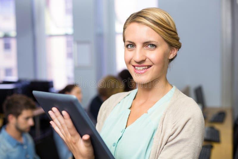 Lärarinna som använder den digitala minnestavlan i datorgrupp royaltyfria bilder