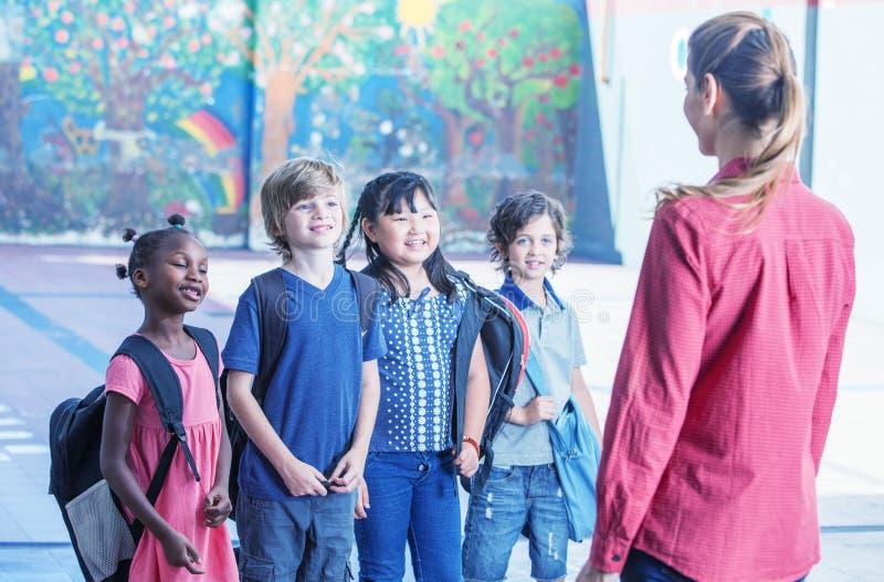 Lärarinna som förklarar till multiracestudenter i schoolyard royaltyfri bild