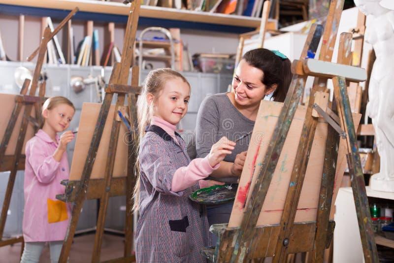 Lärarinna som hjälper studenten under målninggrupp arkivbilder