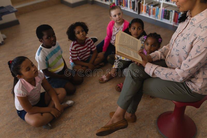 Lärarinna som läser en berättelse till skolbarn royaltyfria foton