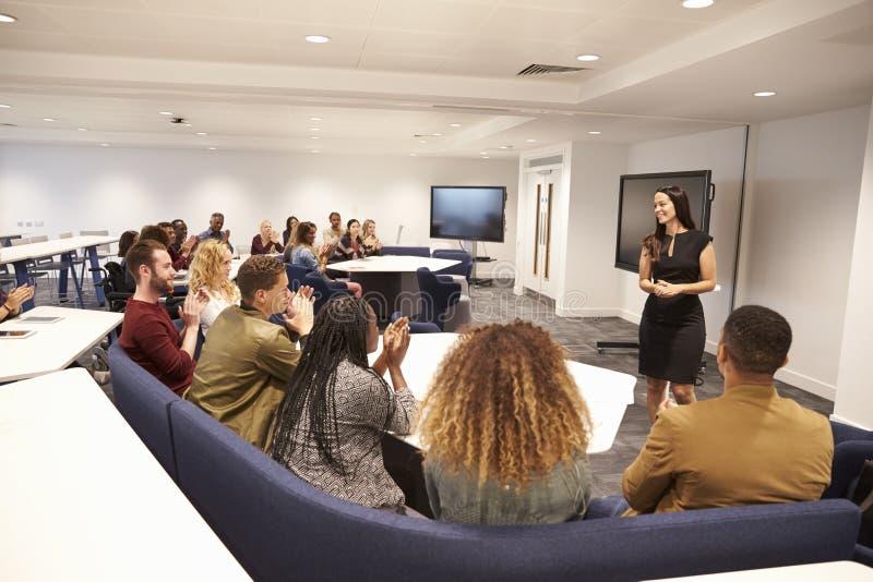 Lärarinna som tilltalar universitetsstudenter i ett klassrum royaltyfri foto