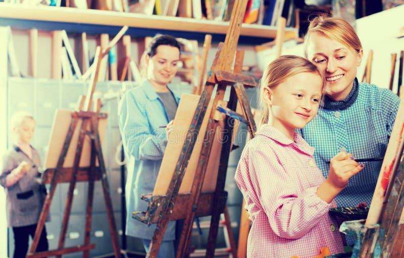Lärarinnaportionflicka under målninggrupp royaltyfri bild
