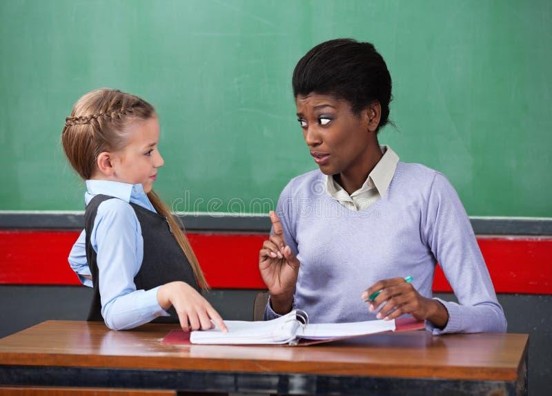 LärarinnaScolding Schoolgirl At skrivbord royaltyfri fotografi