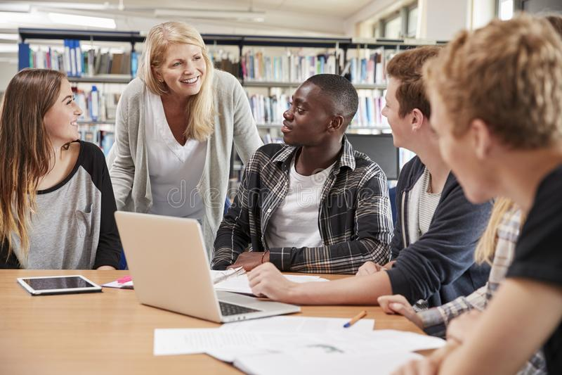 LärarinnaWorking With College studenter i arkiv arkivbilder