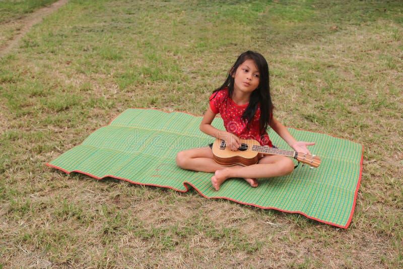 Lärd thailändsk flicka att spela ukulelet arkivfoton