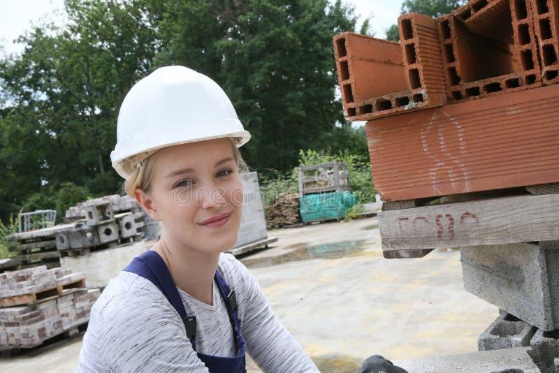 Lärling för ung kvinna i konstruktion royaltyfria bilder