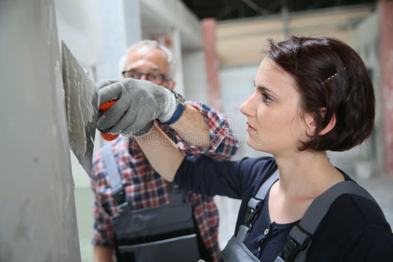 Lärling för ung kvinna i plastery med professor fotografering för bildbyråer