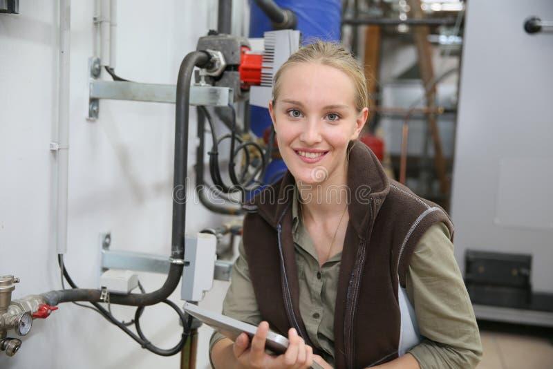 Lärling för ung kvinna som kontrollerar vattennivån fotografering för bildbyråer